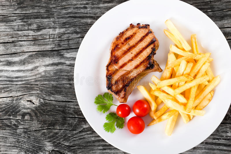 Grilled Pork Chops On A White Dish With French Fries Stock Photo ...