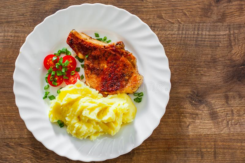 Grilled pork loin with mashed potatoes and salad in white plate on wooden table background with copy space. top view stock photography