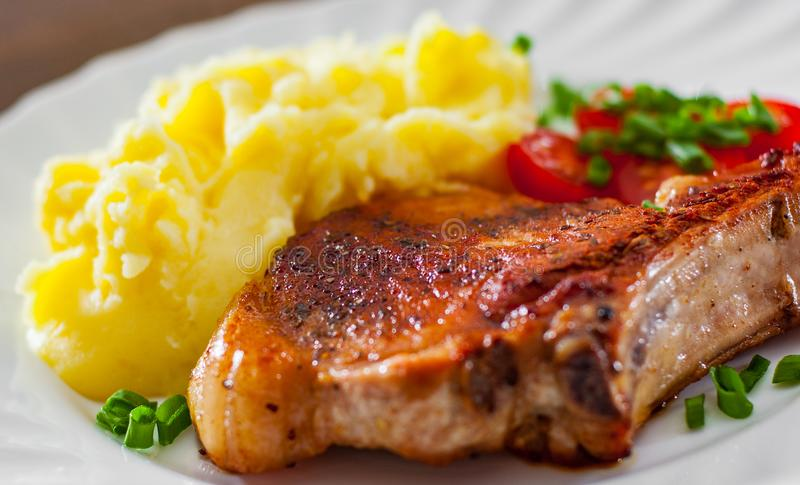 Grilled pork loin meat with mashed potatoes and salad royalty free stock images