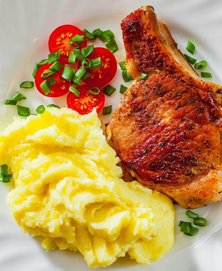 Grilled pork loin meat with mashed potatoes and salad royalty free stock image