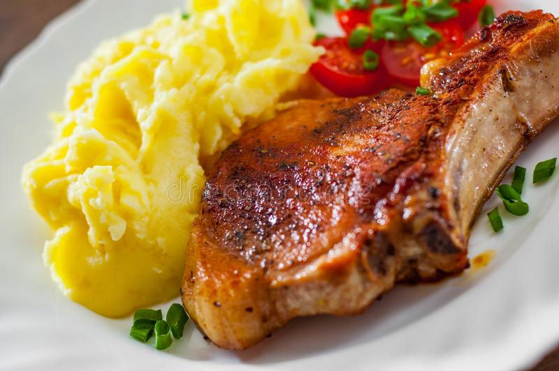 Grilled pork loin meat with mashed potatoes and salad stock images