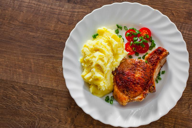 Grilled pork loin with mashed potatoes and salad in white plate on wooden table background with copy space. top view stock images