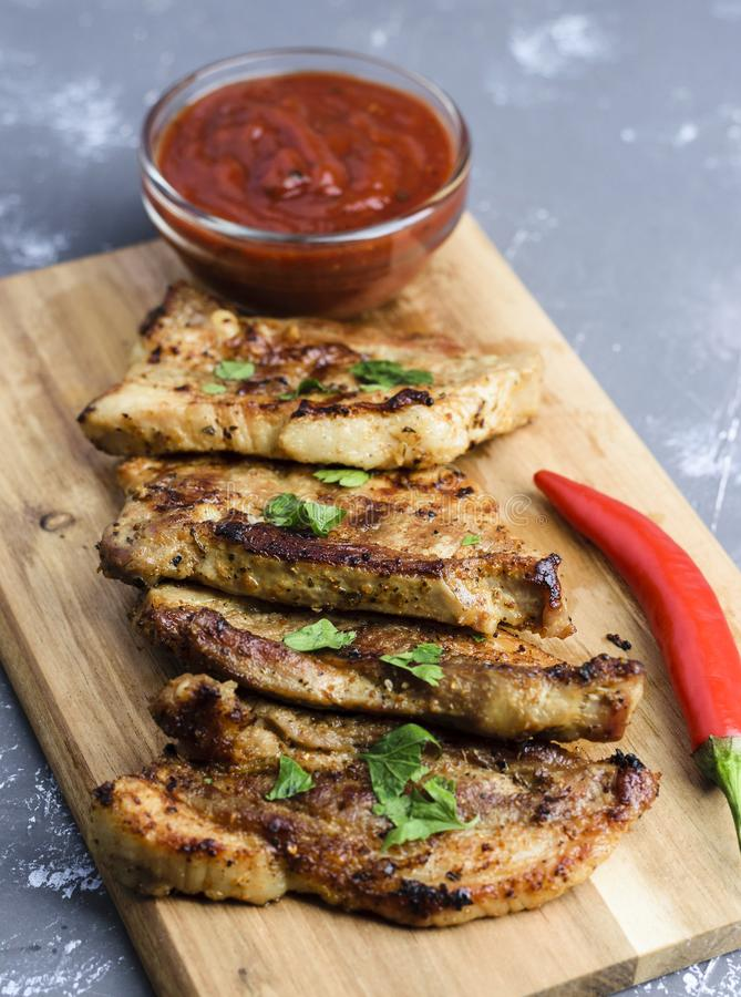 Grilled pork meat. Served on wooden cutting board with chili pepper and ketchup sauce stock image