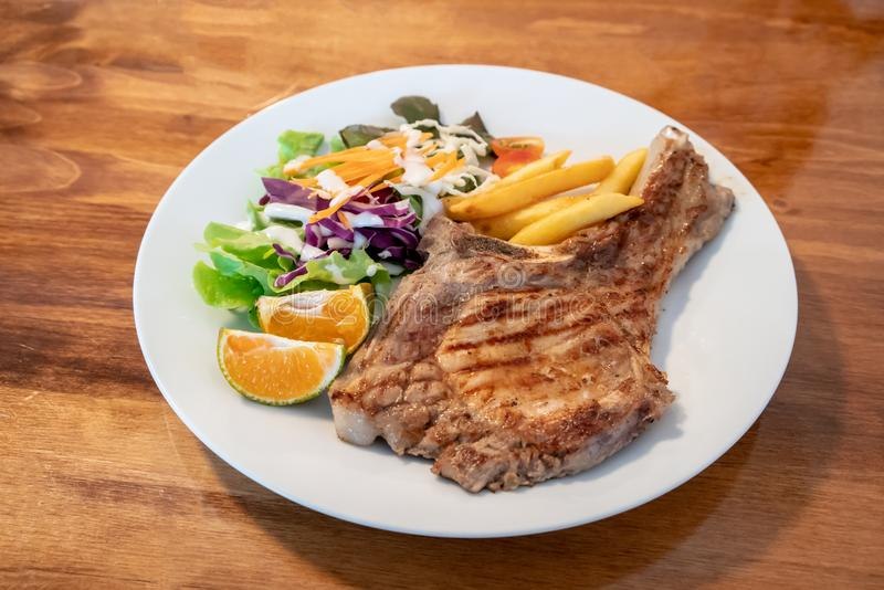 Grilled pork meat steak with oranges and vegetables royalty free stock image