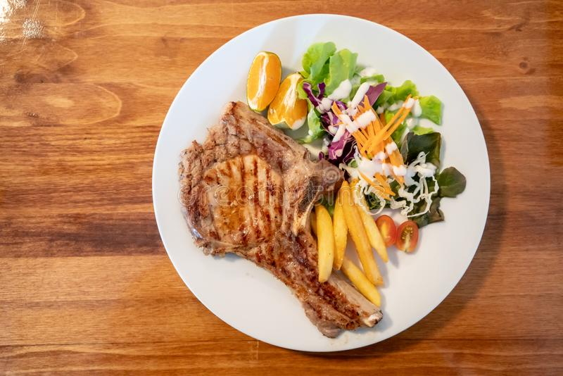 Grilled pork meat steak with oranges and vegetables stock image