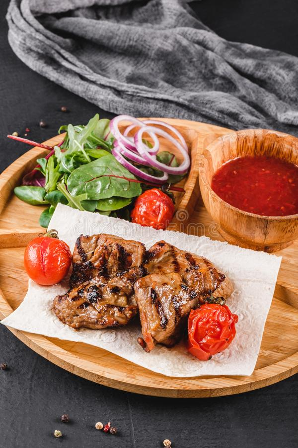 Grilled pork meat and vegetables with fresh salad and bbq sauce on cutting board over black stone background. Hot Meat Dishes.  royalty free stock photos