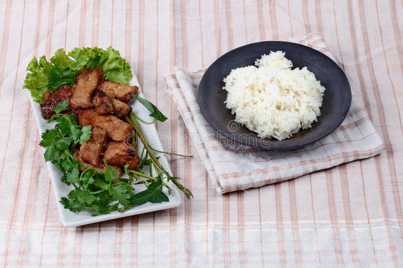 Grilled pork with mixed herb served sticky rice . Grilled pork with mixed herb served morning glory ,coriander and lettuce and sticky rice royalty free stock image