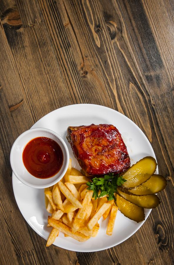 Grilled Pork Rib and Fried Potatoes on White Plate. on a wooden background. with copy space. top stock photo