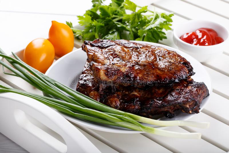 Grilled pork ribs. Meat bbq ribs served with sauce and fresh vegetables.  royalty free stock images