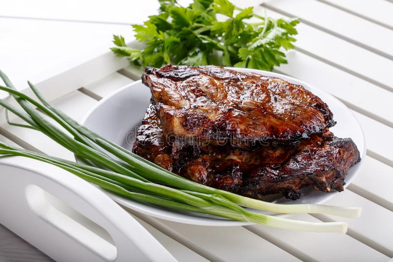 Grilled pork ribs. Meat bbq ribs on white tray royalty free stock photo
