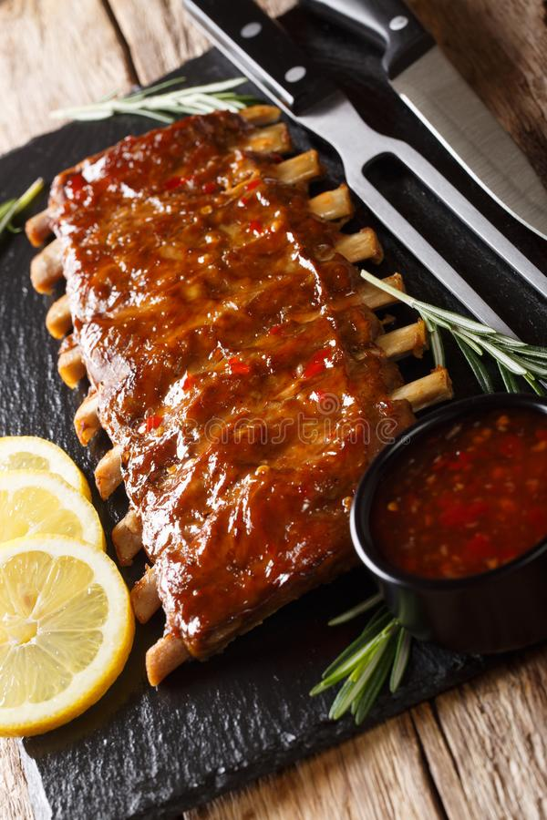 Grilled pork ribs served with chilli sauce and lemon closeup on a slate. vertical stock photography