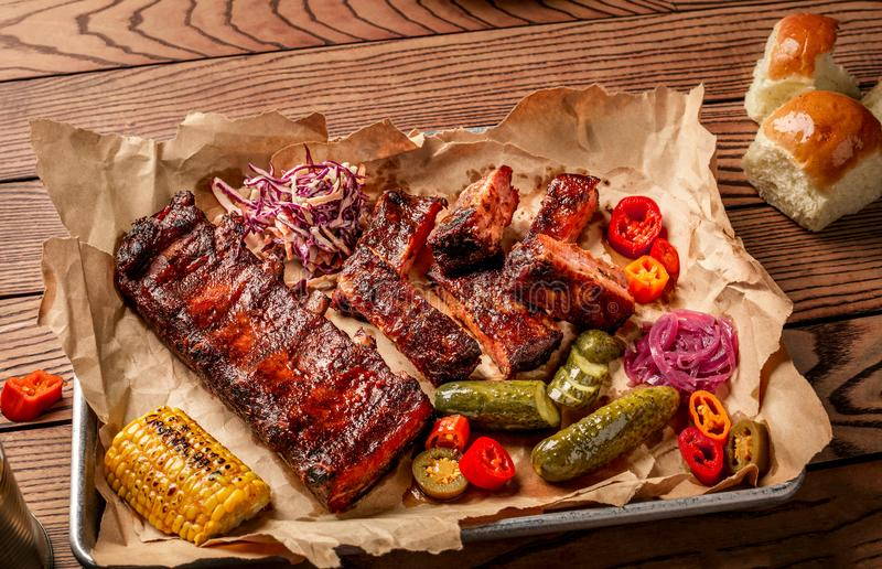 Grilled pork ribs served with grilled corn, salat, bbq sauce, salt pepper and cucumber on parchment paper on a wooden stock photos