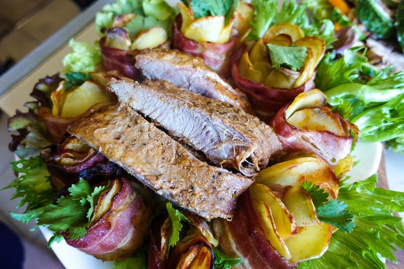 Grilled pork ribs on a white plate with greens, lettuce and meat rolls stock image