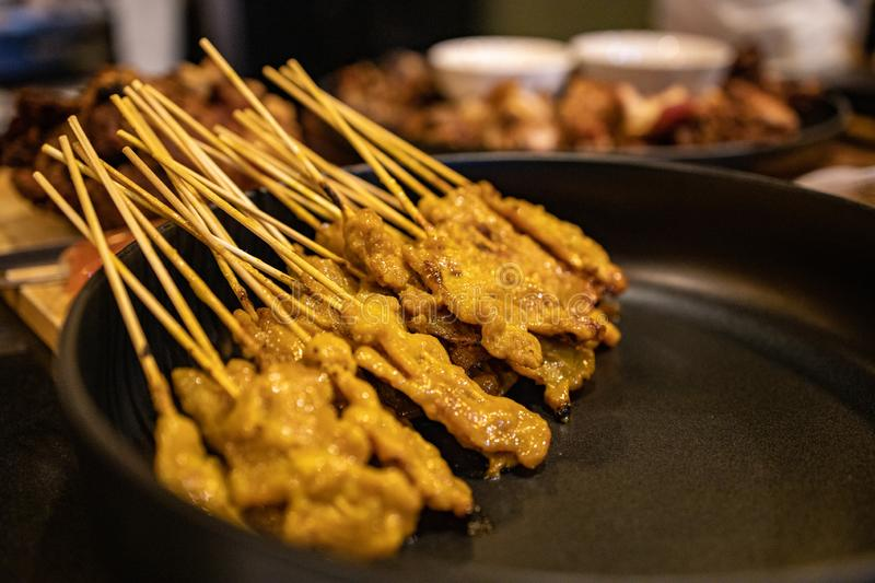 Grilled pork satay on the bamboo stick in a black tray. Thai syle grilled pork satay on a bamboo stick with traditional herb and spices stock photos