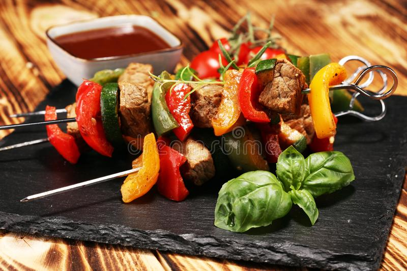 Grilled pork shish or kebab on skewers with vegetables . Food background shashlik royalty free stock photography