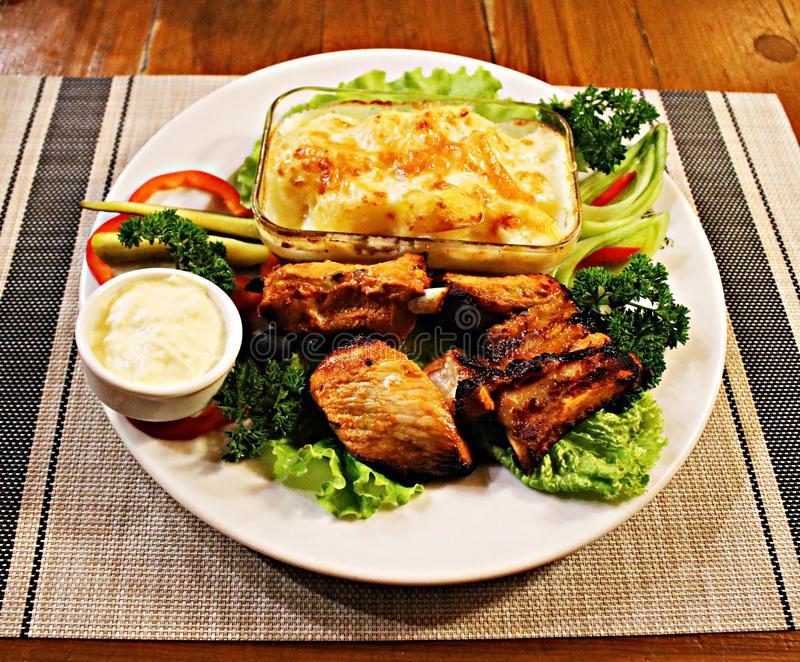 Grilled pork slices, potatoes in a glass bowl and assorted fresh vegetables salad royalty free stock photo