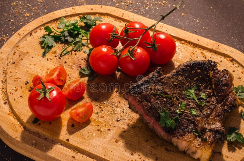 Grilled pork steak with branch of cherry tomatoes royalty free stock photography