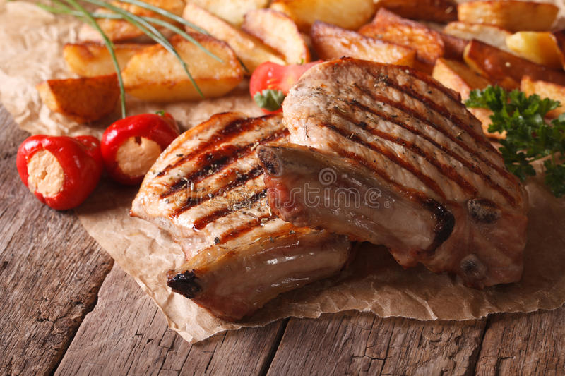 Grilled pork steak with potatoes and vegetables close up on paper. Horizontal, rustic style royalty free stock image