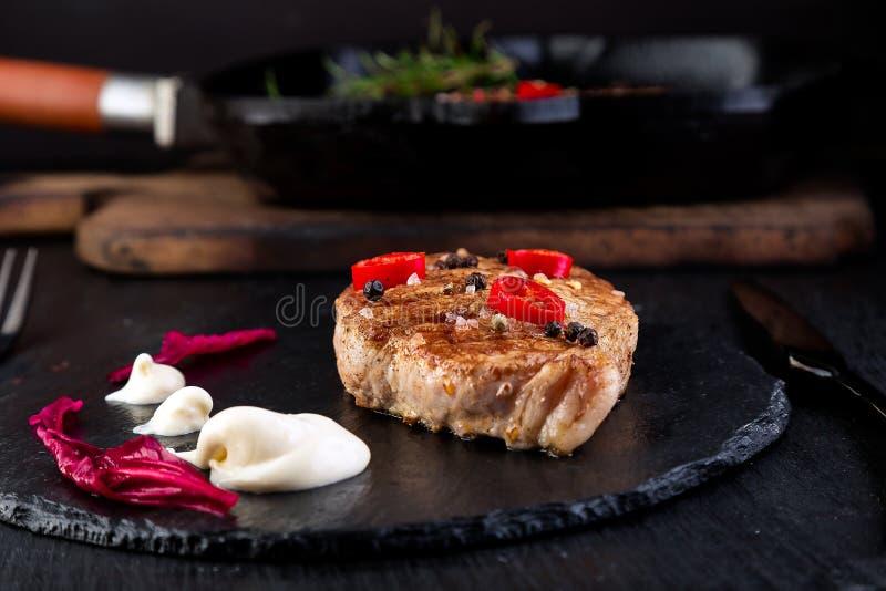 Grilled pork steak on slate plate. Grilled pork steak on slate plate with pepper chilli stock photo