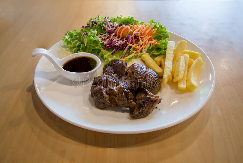 Grilled pork steak and vegetables . plate of grilled pork with french fries and salad on Table. juicy grilled pork chop neck cut. With greens royalty free stock photos