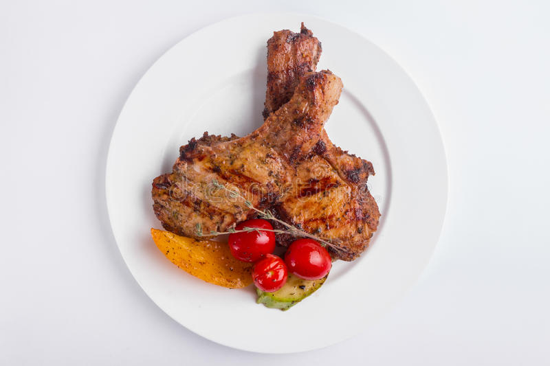 Grilled pork steak and vegetables on a white background stock photography