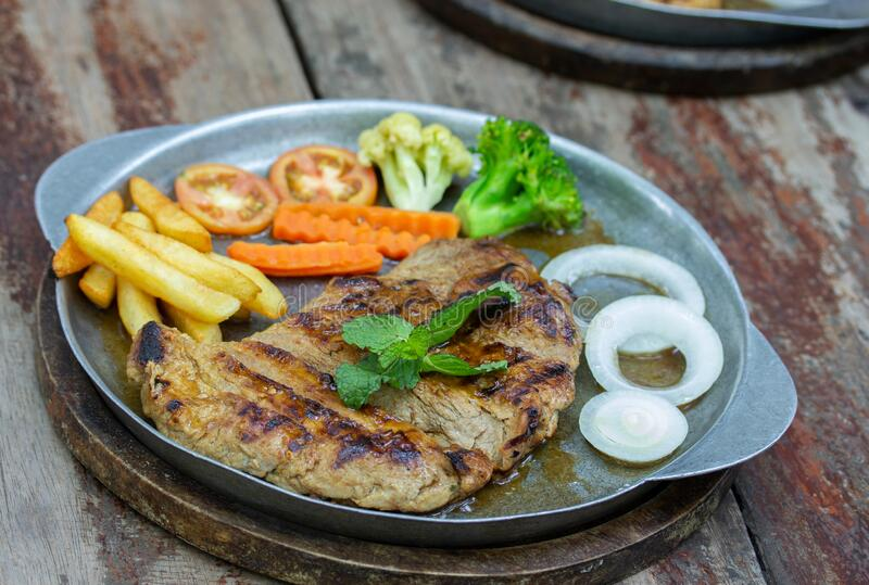Grilled Pork Steaks and French Fries with Vegetable stock photos