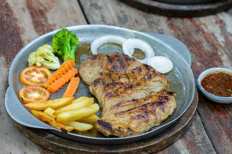 Grilled Pork Steaks and French Fries with Vegetable stock images