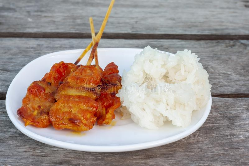 Grilled pork with sticky rice in white plate is a food that Thai people prefer to eat. Grilled pork with sticky rice in white plate is a food that Thai people royalty free stock photography