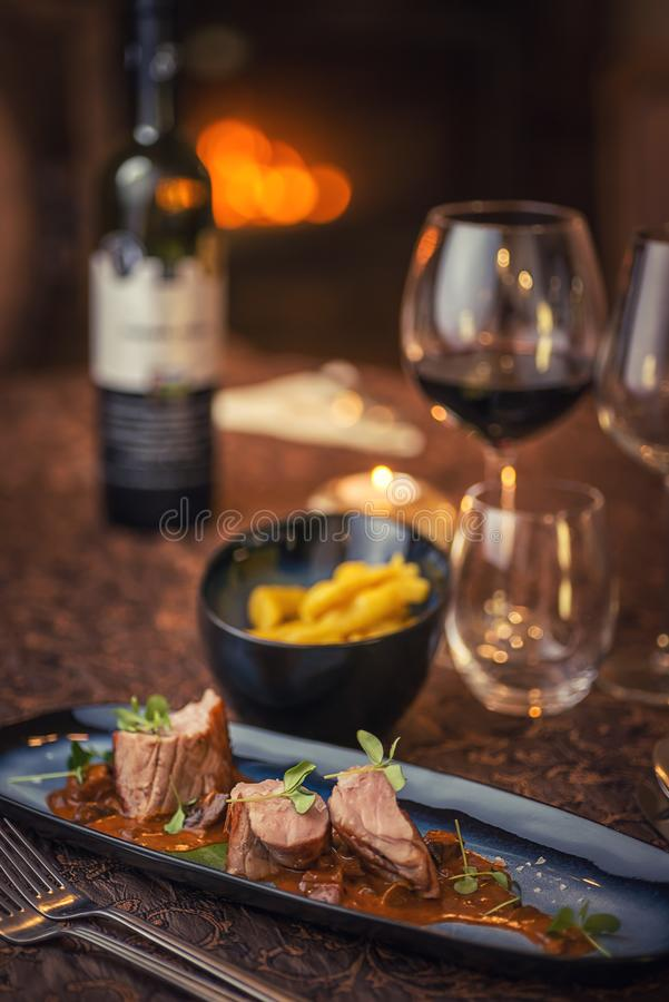 Grilled pork tenderloin with mushroom sauce served on plate with glass of wine and dumplings, modern seasonal gastronomy.  royalty free stock image