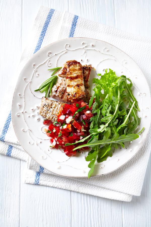 Grilled Pork Tenderloin with Pepper -Tomato Salsa and Arugula Salad royalty free stock image