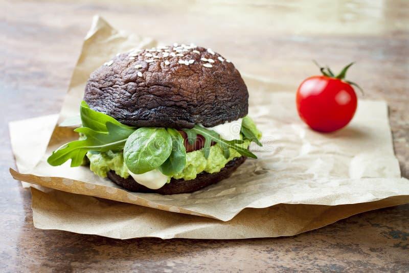 Grilled portobello bun mushroom burger. Vegan, gluten free, grain free, healthy veggies hamburger with guacamole, fresh vegetables. And cashew cheese sauce stock photography