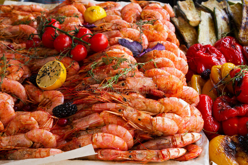 Grilled prawns, lemon and vegetables being served on food stall on open kitchen international food festival event of street food.  stock photo