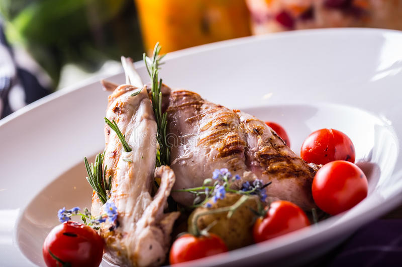 Grilled rabbit leg with rosemary and vegetable decoration royalty free stock photos