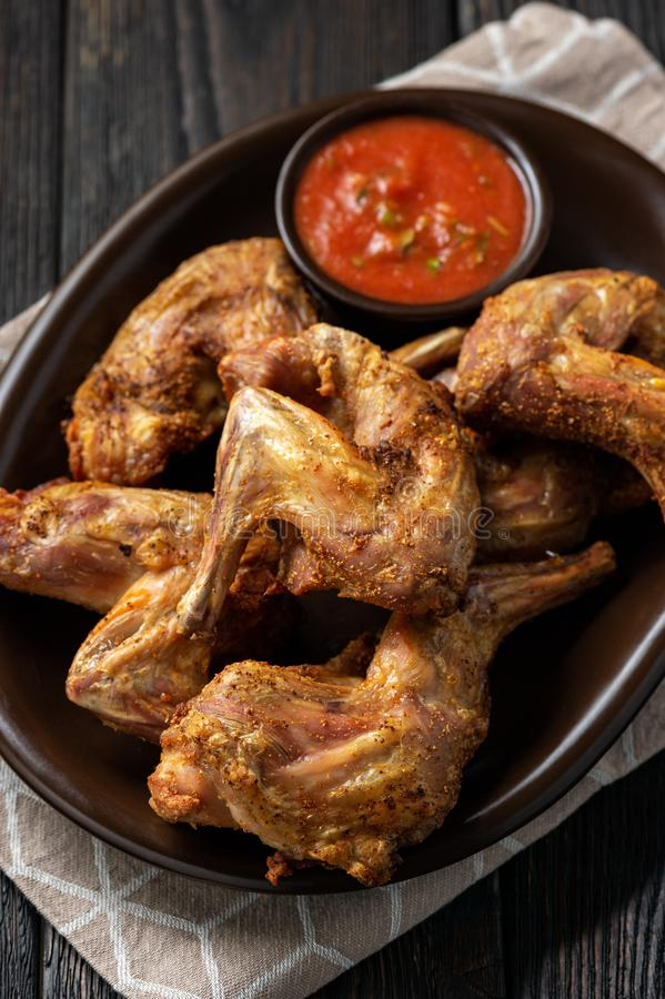 Grilled rabbit legs with spicy tomato dip. stock photos