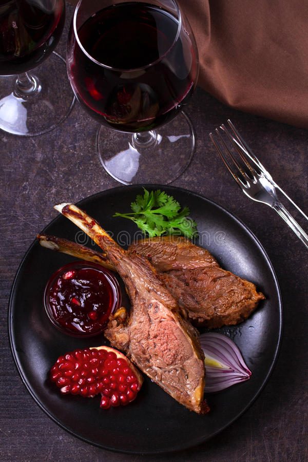 Grilled rack of lamb with pomegranate sauce in black plate royalty free stock images