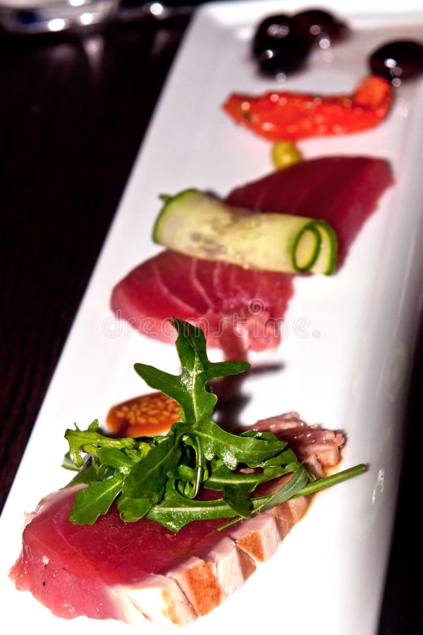 Grilled and raw tuna-fish on white plate. Dressed up stock photos