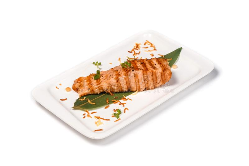Grilled red fish steak on a bamboo leaf in a rectangular plate on an isolated white background royalty free stock image