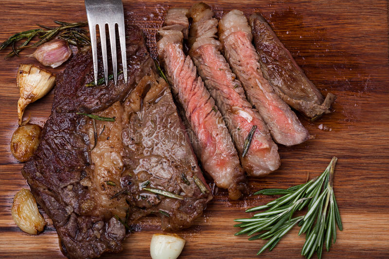 Grilled rib-eye steak of marble beef closeup with spices on a wooden Board. Juicy steak medium rare, sliced and ready to eat royalty free stock photos
