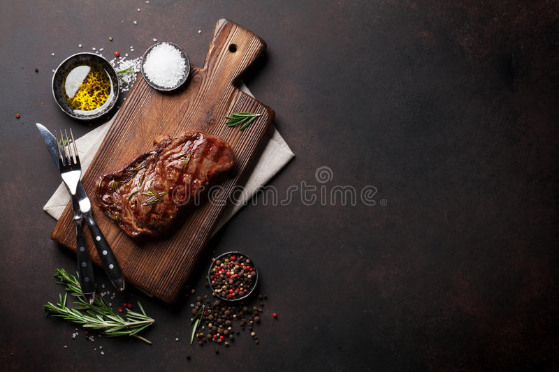 Grilled ribeye beef steak, herbs and spices. Top view with copy space for your text royalty free stock photo