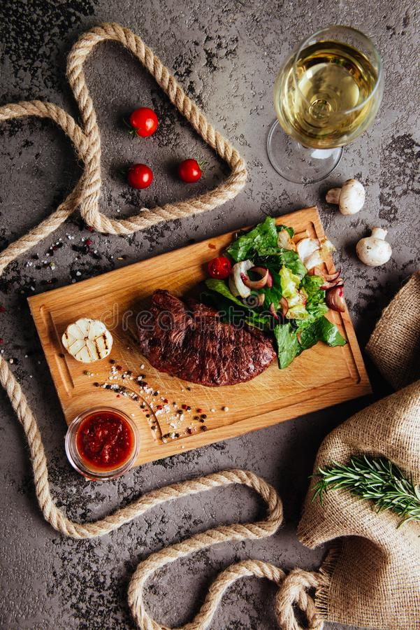 Grilled ribeye beef steak with red wine, herbs and spices on a dark stone background. Top view with copy space for your text stock photography
