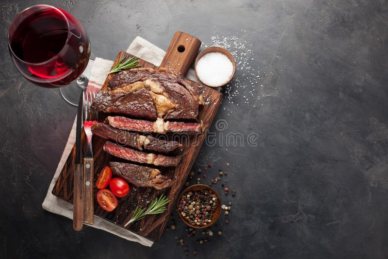 Grilled ribeye beef steak with red wine, herbs and spices on a dark stone background. Top view with copy space for your. Text royalty free stock photo