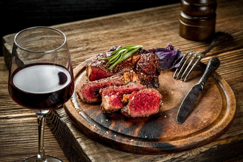 Grilled ribeye beef steak with red wine, herbs and spices on wooden table stock image