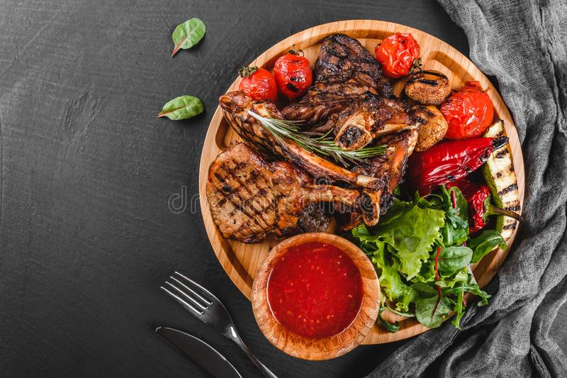 Grilled Ribeye Steak on bone and vegetables with fresh salad and bbq sauce on cutting board over black stone background. Hot Meat. Dishes stock photo