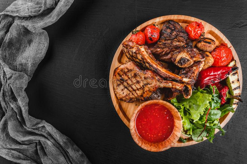 Grilled Ribeye Steak on bone and vegetables with fresh salad and bbq sauce on cutting board over black stone background. Hot Meat Dishes royalty free stock photography