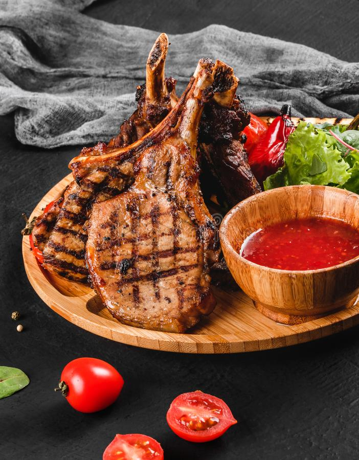 Grilled Ribeye Steak on bone and vegetables with fresh salad and bbq sauce on cutting board over black stone background. Hot Meat Dishes stock photos