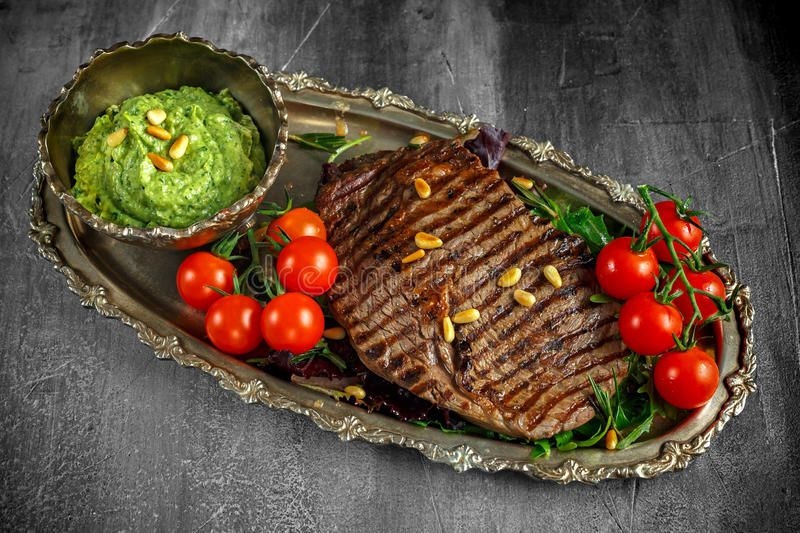 Grilled Ribeye steak served on salad pillow with pesto, pine nuts and cherry tomatoes on a vitage plate royalty free stock photos