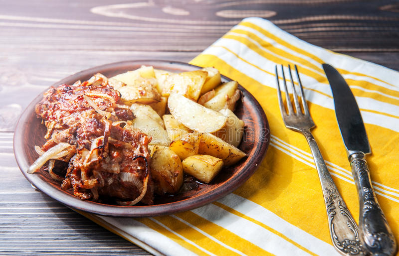 Grilled ribs with barbecue sauce, onion and hot crispy potatoes. Grilled ribs on the plate with barbecue sauce with onion rings and hot crispy potatoes served on royalty free stock photography