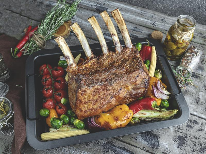 Grilled roasted rack of lamb,mutton with vegetables on the baking sheet.  stock photography