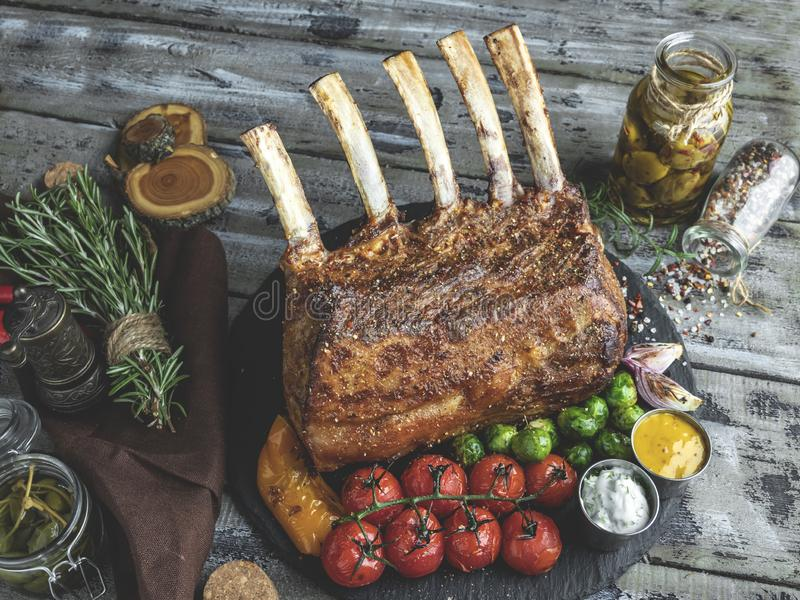 Grilled roasted rack of lamb,mutton with vegetables on a wooden surface.  stock image