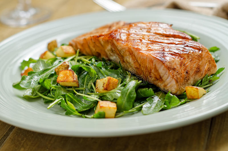 Grilled Salmon. A delicious grilled salmon steak with roast potato and arugula salad stock image